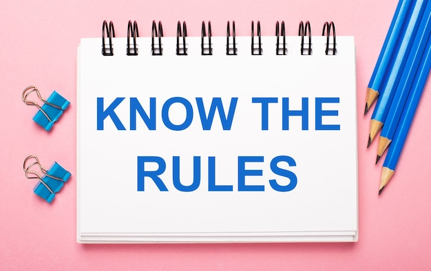 Sur un fond rose clair, des crayons bleu clair, des trombones et un cahier blanc avec le texte connaissez les règles
