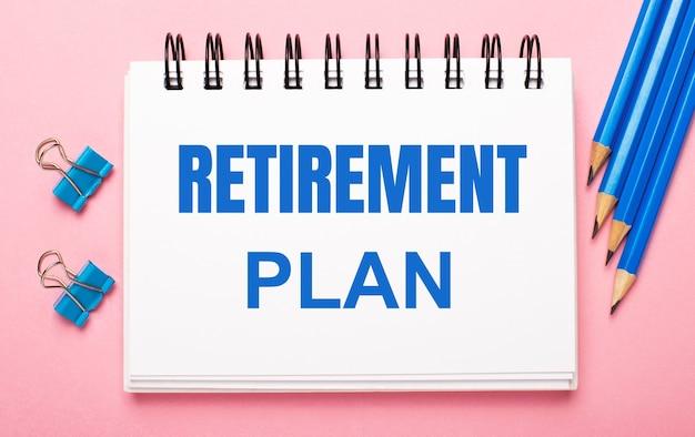 Sur un fond rose clair, des crayons bleu clair, des trombones et un cahier blanc avec le texte plan de retraite