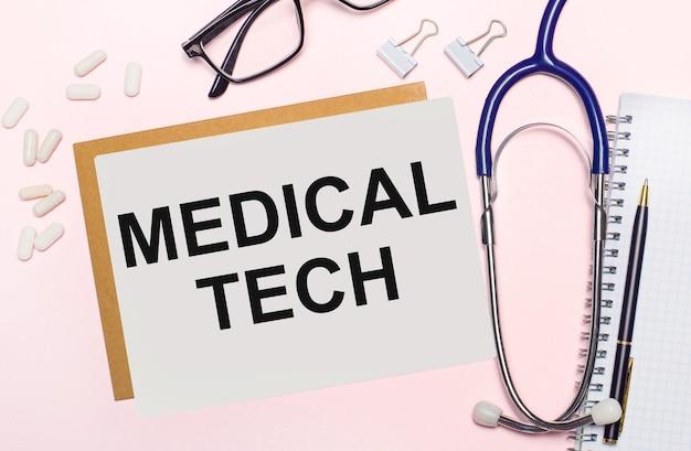 Sur un fond rose clair, un stéthoscope, des pilules blanches et des pinces à papier, des lunettes à monture noire et une feuille de papier avec le texte medical tech. vue d'en-haut. notion médicale
