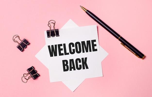 Sur un fond rose clair, des trombones noirs, un stylo noir et du papier à lettres blanc avec les mots bienvenue de retour. mise à plat