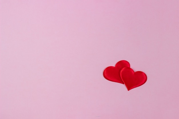 Fond rose avec des coeurs rouges
