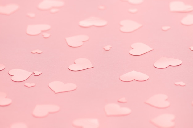 Fond rose avec des confettis de coeurs roses pour la saint-valentin