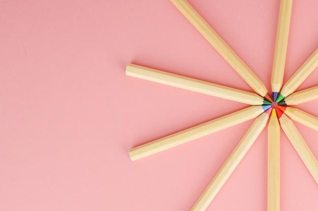 Fond rose avec des crayons colorés ordinaires en bois. retour à l'école.
