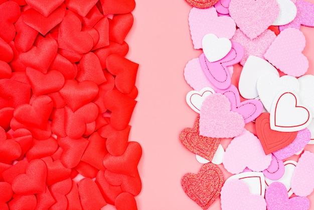 Fond rose encadré de coeurs rouges