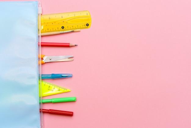 Fond rose et fournitures scolaires multicolores retour à l'école produits à plat pour les écoliers