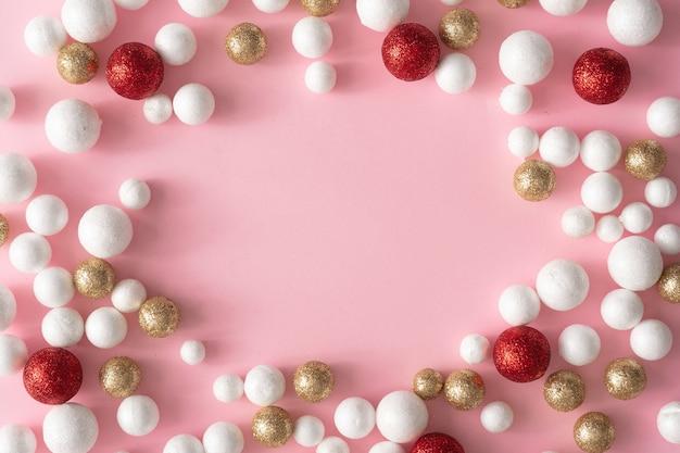 Fond rose de noël avec espace de copie en décoration de boule de paillettes d'or, rouge et blanc. style minimal de fête de carte de voeux de nouvel an. mise à plat