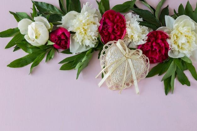 Sur un fond rose des pivoines et un coeur en dentelle
