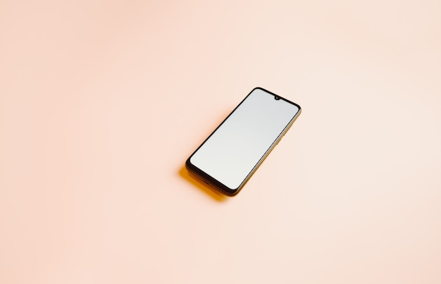 Un fond rose plat avec un téléphone mobile avec un écran blanc et copiez l'espace pour écrire sur