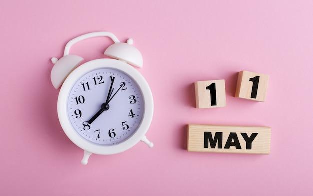 Sur fond rose, un réveil blanc et des cubes en bois avec la date du 11 mai