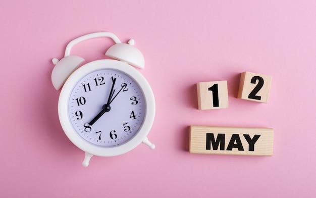 Sur fond rose, un réveil blanc et des cubes en bois avec la date du 12 mai