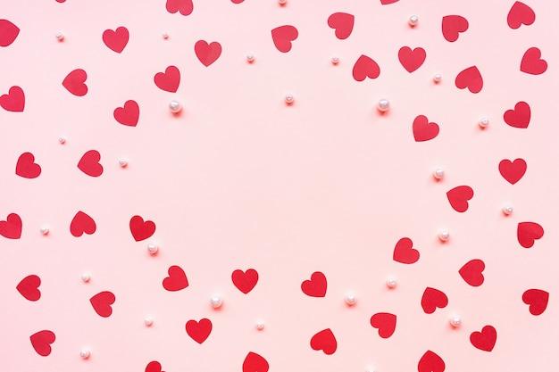 Fond rose romantique avec des coeurs en papier rouge