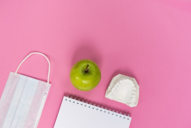 Sur un fond rose se trouve un moulage de dents, une pomme et un masque médical