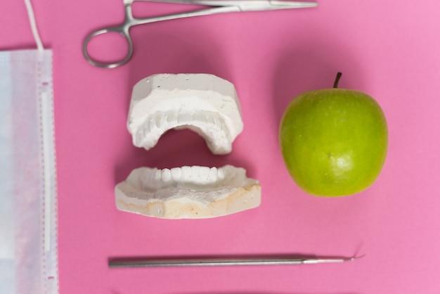 Sur un fond rose se trouvent un moulage de dents, une pomme