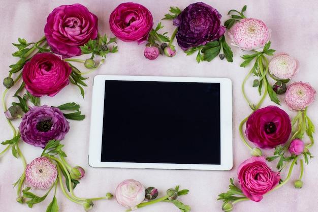 Sur un fond rose sont les fleurs de renoncule et la tablette