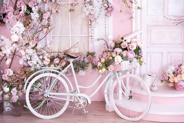 Fond rose. vélo rétro avec des fleurs près du porche, seuil. carte postale romantique.