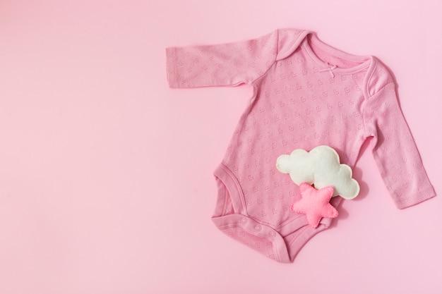 Fond rose avec des vêtements et des jouets pour une fille nouveau-née.