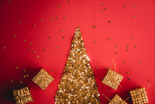 Fond rouge abstrait festif avec de petites étoiles décoratives dorées avec des étincelles.