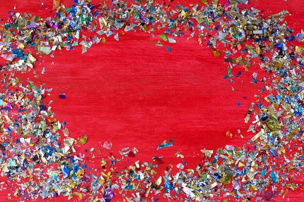 Sur un fond rouge, des confettis dispersés dans un cercle et au milieu