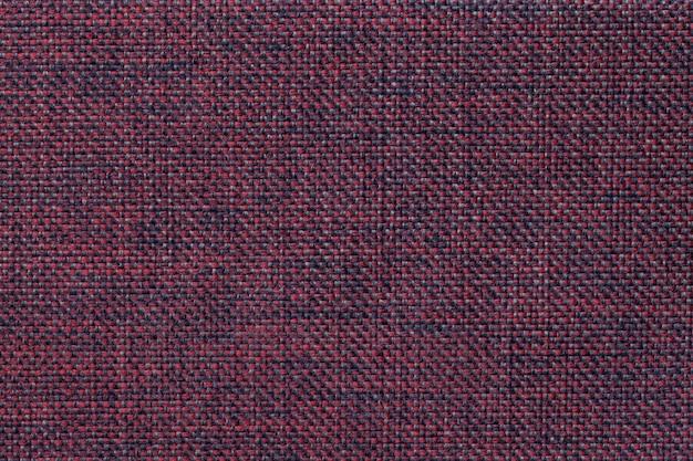 Fond rouge foncé de tissu d'ensachage tissé dense, gros plan.