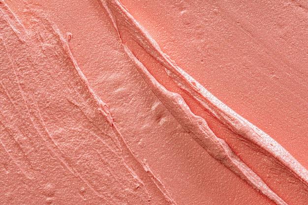 Fond d'un rouge à lèvres de couleur pêche brillant taché