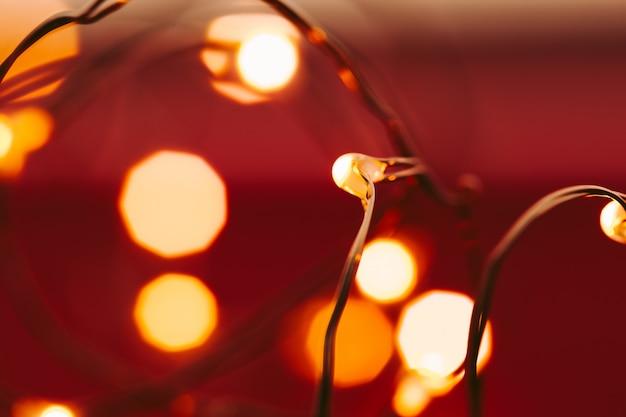 Fond rouge avec des lumières illuminées de guirlande