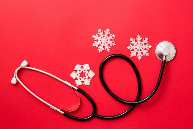 Fond rouge médecine avec stéthoscope et flocons de neige, hiver médical