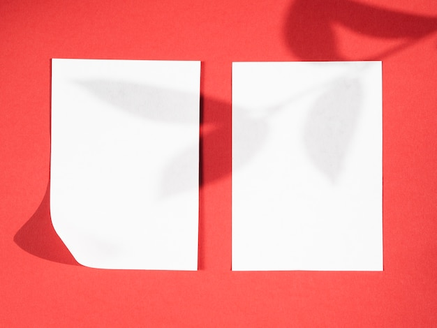 Fond rouge avec une ombre de branche sur deux couvertures blanches