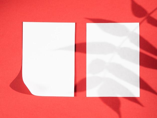 Fond rouge avec des papiers blancs et des ombres de feuilles