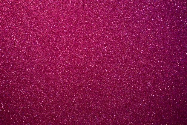 Fond rouge et rose avec des paillettes festives scintillantes.