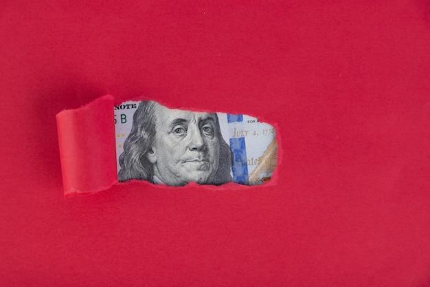 Un fond rouge, sous lequel un portrait représenté sur un billet de cent dollars apparaît.