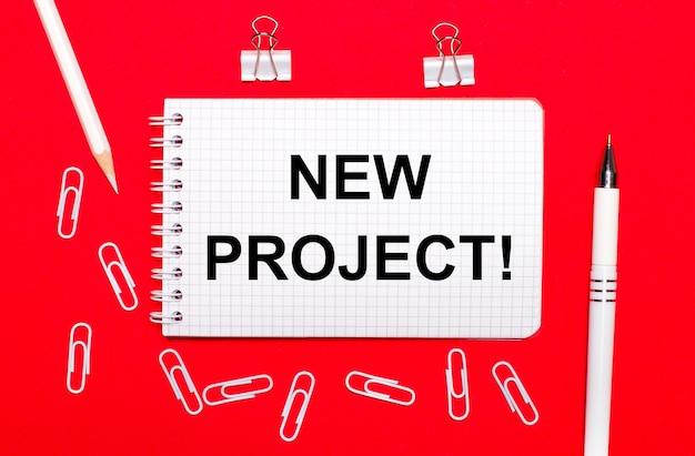 Sur fond rouge, un stylo blanc, des trombones blancs, un crayon blanc et un cahier avec le texte nouveau projet. vue d'en-haut