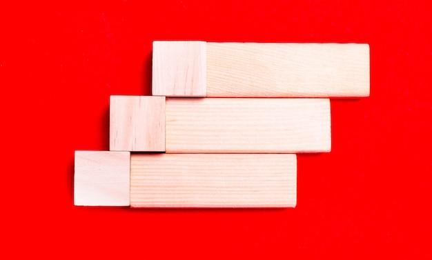 Sur un fond rouge vif, des blocs et des cubes en bois clair avec un emplacement pour insérer du texte.