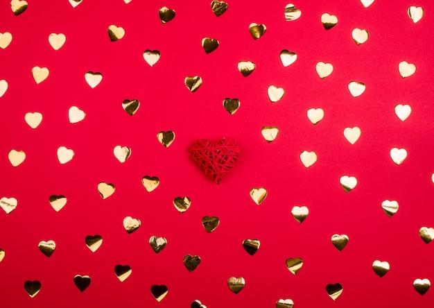 Fond rouge vif avec des coeurs dorés, récipient festif, vacances de tous les amoureux. place pour l'inscription.