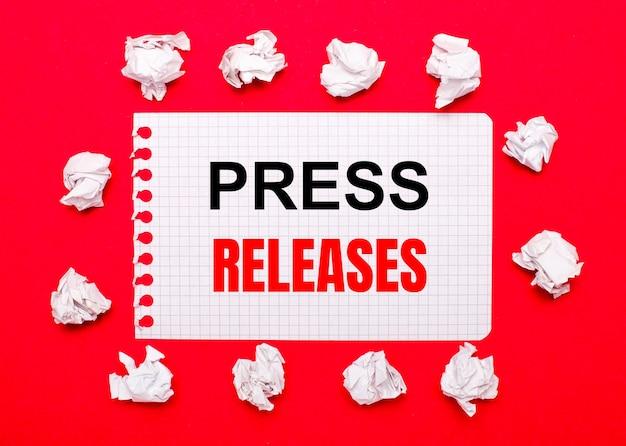 Sur un fond rouge vif, des feuilles de papier froissées blanches et une feuille de papier avec le texte communiqués de presse