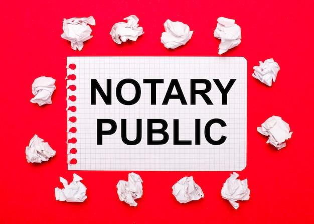 Sur un fond rouge vif, des feuilles de papier froissées blanches et une feuille de papier avec le texte notaire public