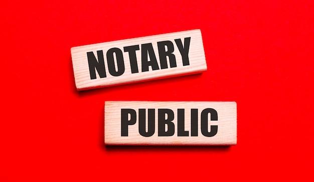 Sur un fond rouge vif, il y a deux blocs de bois clair avec le texte notary public