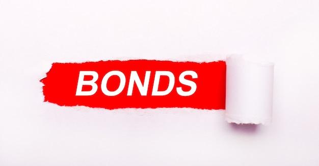 Sur fond rouge vif, papier blanc avec une rayure déchirée et l'inscription bonds.