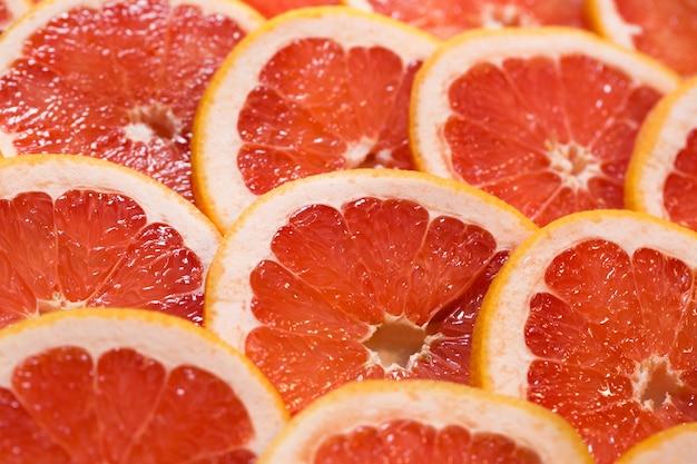 Fond rouge vif avec des tranches juteuses de pamplemousse. contexte alimentaire sain.