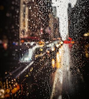 Fond de rue floue de la ville de new york avec des gouttes d'eau, des lumières et des voitures à l'heure du soir pluvieux