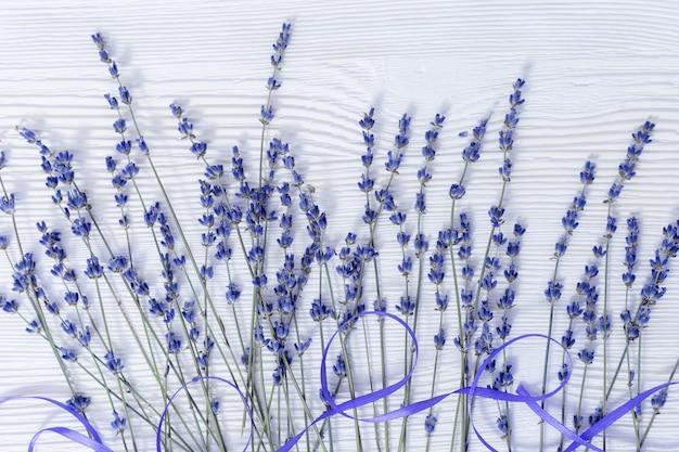 Fond rustique avec des fleurs de lavande sur une surface en bois blanche. mise au point sélective.