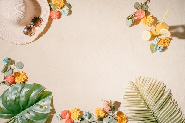 Fond de sable de plage avec un chapeau grandes lunettes de soleil jus de fruits avec des morceaux de citron fleurs colorées et feuilles de coco et de palmier été et vacances concept copy space