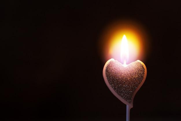 Fond de saint-valentin avec bougie allumée en forme de coeur avec flamme chaude