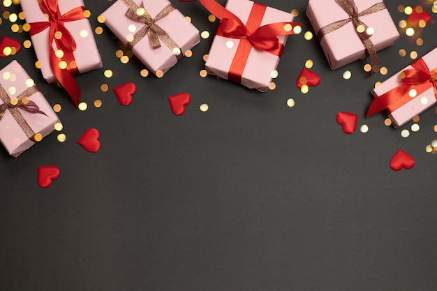 Fond de saint valentin avec cadeau surprise et rubans d'or, forme d'amour rouge sur fond sombre