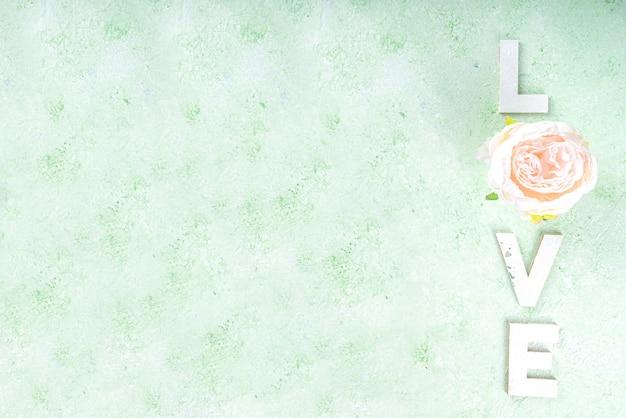 Fond de saint valentin, carte de voeux ou invitation. lettres d'amour avec fleur, vue de dessus sur fond de printemps vert clair flatlay