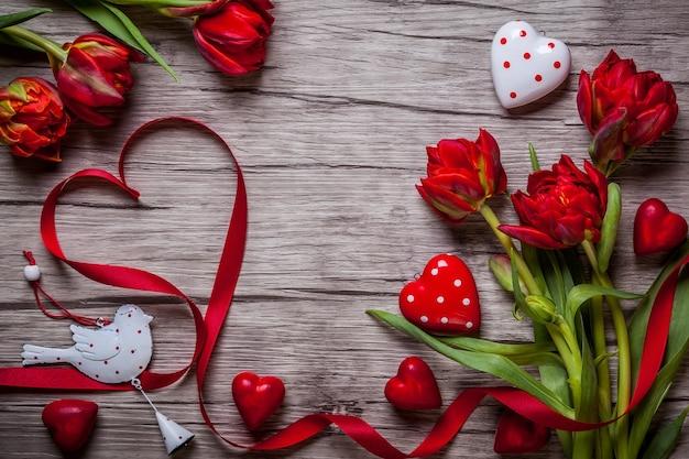 Fond de saint valentin avec des chocolats, des coeurs et des tulipes rouges