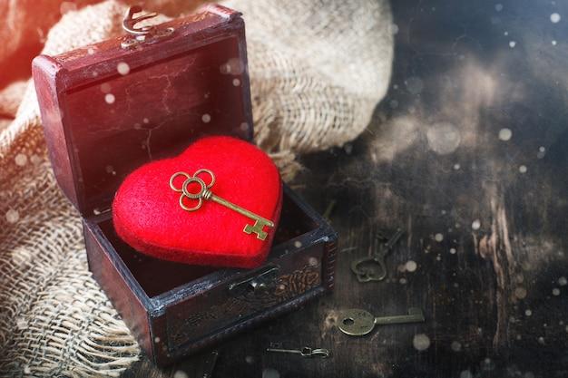 Fond de saint valentin avec un coeur et une clé ancienne sur table en bois.