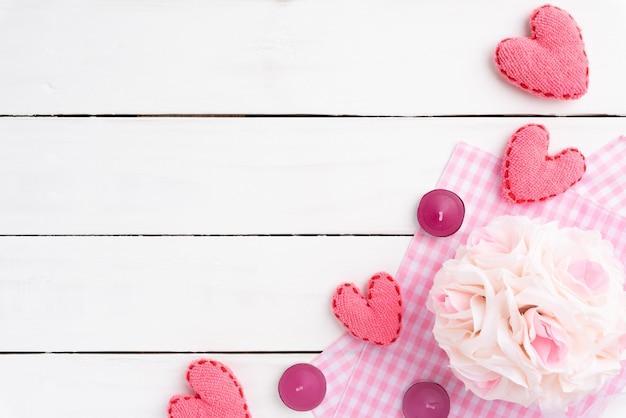 Fond saint valentin, coeur rose avec des bougies et des fleurs sur fond en bois.
