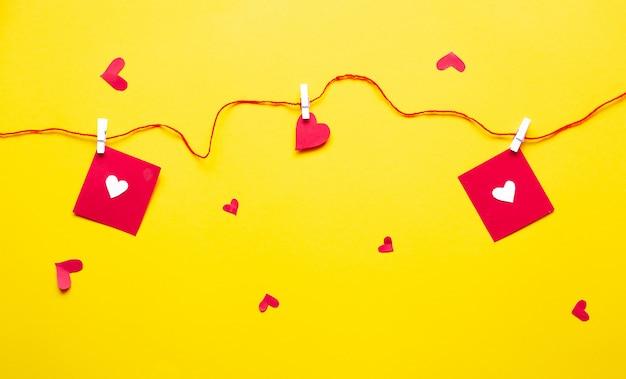 Fond de la saint-valentin avec coeurs rouges et accessoires sur fond jaune. fond de formes d'amour.