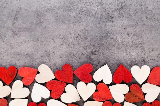 Fond de saint valentin avec des coeurs rouges de fin blanche sur fond en bois.