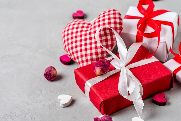 Fond de saint valentin avec coffrets cadeaux, coeurs et fleurs séchées sur fond de béton gris. fermer